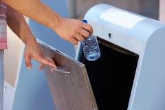La mano dell'uomo che getta via la plastica imbottiglia il recipiente di riciclaggio Fotografie Stock