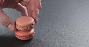 La mano dell'uomo che impila i macarons rosa della fragola sull'ardesia imbarca Immagine Stock Libera da Diritti
