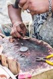 La mano dell'uomo che martella carattere sul braccialetto di cuoio Fotografie Stock Libere da Diritti