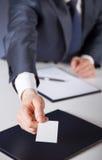 La mano dell'uomo che raggiunge fuori un biglietto da visita Fotografia Stock Libera da Diritti