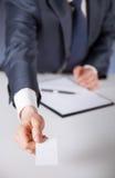 La mano dell'uomo che raggiunge fuori un biglietto da visita Immagine Stock Libera da Diritti