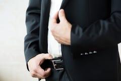 La mano dell'uomo che tiene la cinghia Fotografia Stock