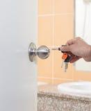 La mano dell'uomo che tiene le chiavi apre la porta Fotografia Stock