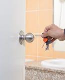 La mano dell'uomo che tiene le chiavi apre la porta Fotografia Stock Libera da Diritti