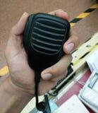La mano dell'uomo che tiene microfono tenuto in mano Immagine Stock