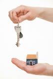 La mano dell'uomo che tiene un mazzo di chiavi e di casa del giocattolo Immagine Stock