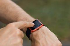 La mano dell'uomo che utilizza un orologio astuto per osservare i messaggi ricevuti e le chiamate ad un telefono cellulare che si immagine stock