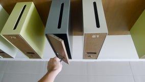La mano dell'uomo con la chiave che sblocca un contenitore di posta Vista del primo piano immagini stock