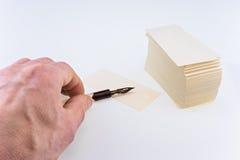 La mano dell'uomo con una vecchia penna e le carte del Libro Bianco immagini stock