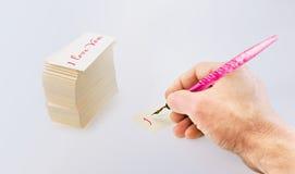 La mano dell'uomo con una vecchia penna e le carte del Libro Bianco immagini stock libere da diritti