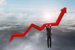 La mano dell'uomo d'affari che appende sul grafico rosso di tendenza con luce del giorno si appanna Fotografia Stock Libera da Diritti