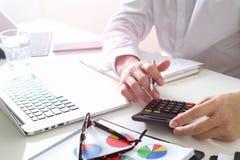 la mano dell'uomo d'affari che funziona con le finanze circa costo e calcola Fotografia Stock