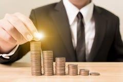 La mano dell'uomo d'affari che mette la pila della moneta aumenta l'aumento risparmia i soldi, Fotografia Stock
