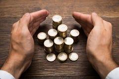 La mano dell'uomo d'affari che protegge le euro monete Fotografia Stock