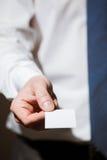 La mano dell'uomo d'affari che raggiunge fuori un biglietto da visita Fotografia Stock