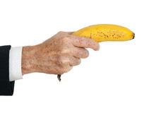 La mano dell'uomo d'affari con la banana gradice la pistola, sopra bianco Immagine Stock