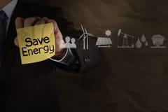 La mano dell'uomo d'affari disegna l'energia di risparmi sulla nota appiccicosa con le icone e Fotografia Stock