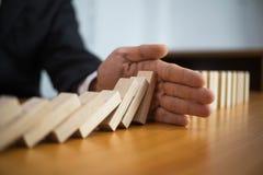 La mano dell'uomo d'affari ferma il significato capovolto continuo di domino che ha ostacolato il fallimento Faccia tappa questo  fotografie stock