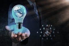 La mano dell'uomo d'affari mostra la lampadina con il netwo del sociale del pianeta Terra Immagini Stock