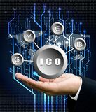 La mano dell'uomo d'affari porta il simbolo di ICO con la parte posteriore dell'albero del circuito digitale Immagine Stock