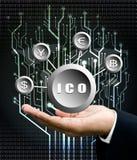 La mano dell'uomo d'affari porta il simbolo di ICO con la parte posteriore dell'albero del circuito digitale Fotografia Stock