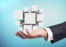 La mano dell'uomo d'affari presenta il gruppo di cubi in palma aperta rappresentazione 3d Immagine Stock