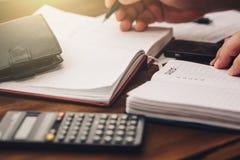 La mano dell'uomo d'affari tiene la penna che lavora al calcolatore ed ai blocchi note per calcolare il bilancio, concetto finanz Fotografia Stock Libera da Diritti