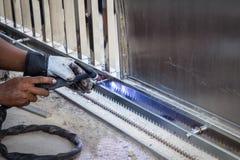 La mano dell'uomo del lavoratore che salda una struttura di porta di acciaio inossidabile dentro si batte Fotografie Stock Libere da Diritti