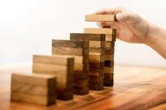 La mano dell'uomo di affari ha messo i blocchi di legno che sistemano l'impilamento per il devel Fotografia Stock Libera da Diritti