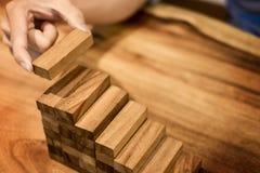 La mano dell'uomo di affari ha messo i blocchi di legno che sistemano l'impilamento per il devel Immagine Stock
