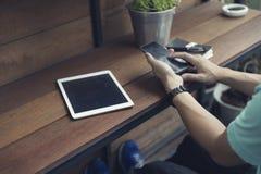 la mano dell'uomo facendo uso dello smartphone con la compressa digitale Immagine Stock Libera da Diritti