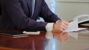 La mano dell'uomo firma un documento cartaceo con la penna a sfera La firma è falsificazione Immagini Stock Libere da Diritti