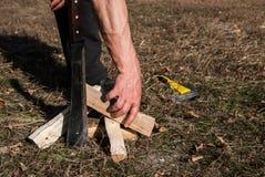 La mano dell'uomo forte prende la legna da ardere per dare fuoco fotografia stock libera da diritti