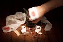 La mano dell'uomo ha tagliato il vetro a pezzi rotto sul legno di buio del fondo immagini stock libere da diritti