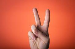 La mano dell'uomo isolata sul fondo di rosso arancio Immagini Stock Libere da Diritti