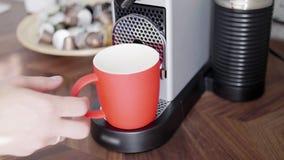 La mano dell'uomo mette la tazza rossa sul vassoio di piccola macchina automatica del caffè con i baccelli video d archivio
