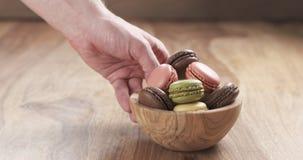 La mano dell'uomo porta la ciotola con i macarons misti di colori sulla tavola Fotografia Stock