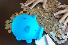 La mano dell'uomo raccoglie la moneta dei soldi nel porcellino salvadanaio blu fotografia stock
