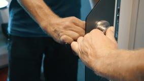 La mano dell'uomo sblocca un fermo ed apre una porta dello specchio con la maniglia del metallo Uscite dell'uomo un compartimento stock footage