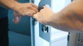 La mano dell'uomo sblocca un fermo ed apre una porta dello specchio con la maniglia del metallo Uscite dell'uomo un compartimento archivi video