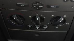 La mano dell'uomo spinge il bottone di controllo di clima dell'automobile Freddo e aria calda di temperatura del regolatore risca video d archivio