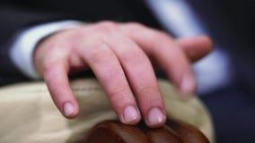 La mano dell'uomo sta trovandosi sul signore del bracciolo che tamburella le sue dita video d archivio