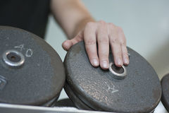 La mano dell'uomo sul peso della testa di legno Immagine Stock