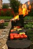 La mano dell'uomo tiene le verdure sulla griglia Immagine Stock