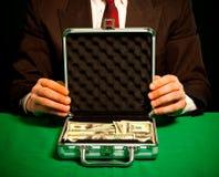 La mano dell'uomo tiene una valigia con i dollari Fotografia Stock