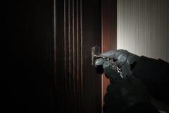 La mano dell'uomo in una chiave del guanto apre la porta Fotografia Stock