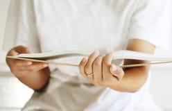 La mano della donna apre un libro Fotografia Stock