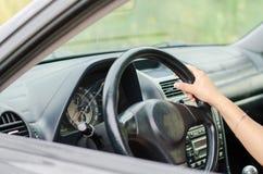 La mano della donna che conduce un'automobile Fotografie Stock