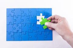 La mano della donna che dispone il pezzo del puzzle fuori dai sig differenti di colore Immagini Stock Libere da Diritti