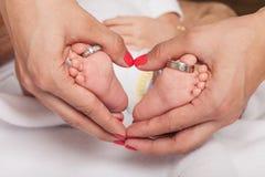 La mano della donna che forma il cuore intorno al piede di un bambino con le fedi nuziali parents fotografia stock